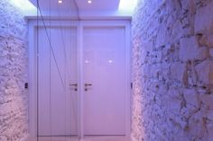 corridoio con specchi e pietre dipinte di bianco #atmosfere #interiordesign #white #blulight