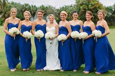bridal party in strapless blue dresses holding white hydrangea bouquets