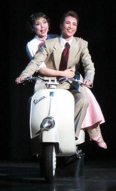 バイクは制作発表で乗ったのが初という。後方はアン王女役の咲妃みゆ
