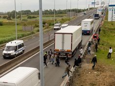"""Hundreds of refugees and migrants have stormed a motorway leading to the port at Calais in desperate attemptsto board lorries heading for the UK. Riot police were sent to the incident near the """"Jungle"""" camp on Wednesday morning, firing tear gas and attempting to force asylum seekers off the road."""