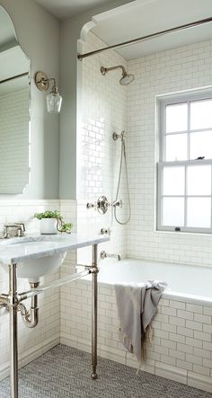 As in the master bath and powder room, the washstand in the daughter's bathroom is by Waterworks. Tiles by Pratt & Larson line the walls, while Ann Sacks herringbone Carrara tiles cover the floor.