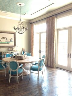 The wallpapered ceiling and bright blue chairs are given centre stage in this light, spacious dining room.