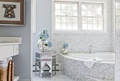 "JD Interiors (""Curved master bathroom features blue walls framing curved vanity with shelf topped with white marble countertop next to white and grey marble tiled bathtub with ceiling height marble backsplash next to metal Moroccan table."")"