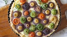 Elegant carrot and zucchini roses are tucked into a savory 3-cheese filling in this show-stopping puff pastry tart perfect for brunch.