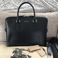 $1995 NWT Burberry Barrow Borsa Black Saffiano Bag This is still IN STORES! And can be purchased on Burberry Website for $1995. Burberry Barrow Borsa Black Bag. It is gorgeous saffiano leather with silver hardware. This is actually a mans bag but I purchased for myself because I love the clean lines and structure. I was told that other women have also purchased this for themselves as well. There is a detachable nylon strap, zipper closure, inside zipper pocket and two sidewall pockets. Does…