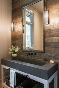 In this rustic modern bathroom, a wood accent wall has been included in the design and an all-in-one concrete vanity and sink sit on a white frame. #Bathroom #RusticModern