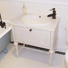 """End Table Sink Vanity """"To make this vintage-inspired vanity, we rescued a flea market end table that had sturdy turned legs. After painting the piece and coating it with polyurethane, we installed the sink basin and faucet. The plumbing and drain are hidden inside the vanity; to access them, we just have to open the door."""""""