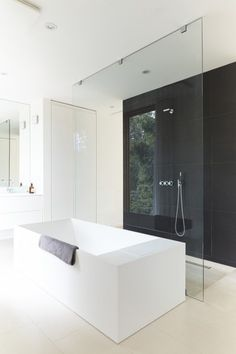 Minimalist Bathroom // white oversized tub with modern glass shower and dark…