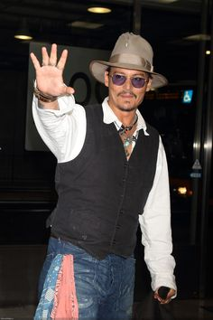 Johnny Depp waves to fans at the Narita International Airport in Tokyo, Japan on 7/16/13 when he arrived to promote The Lone Ranger in Japan.