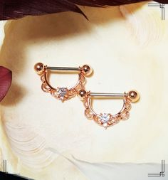 PLEASE READ REFUND/RETURN POLICY BELOW BEFORE YOU PURCHASE Beautiful GENUINE Clear Swarovski Crystals in a rose gold ornate victorian style setting. 316L surgical steel with 5/8 wearable length. You can purchase the individually (1 piece) or you can purchase a set (2 pieces). VIBRANT Shield with barbell Nipple Rings. :) Description: Rose Gold Ornate Nipple Shields Bar Length: 5/8 wearable Material Type: Surgical Steel 316L Gauge: 14g Pleas let me know if you have a special request regardi...