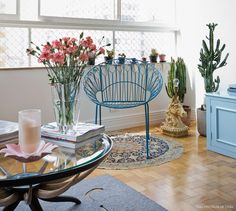 Cadeira de ferro azul e diversas plantas dão charme a esse cantinho no estar.