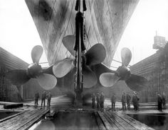 The three steam-powered propellers of the RMS Titanic in dry dock
