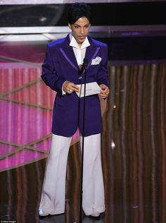 Wearing purple again with white Prince walks on stage during the 77th Annual Academy Awards on February 27, 2005 in Hollywood, in a sharp tailored suit that manages to combine the disco suits of the Seventies and gangsters' tailoring from the Twenties and Thirties