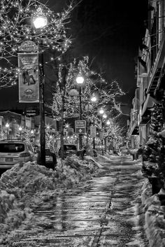 Looking along the snowy sidewalk at the Christmas street lights in black and white in downtown Oakville.