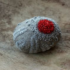 stitched stone by Lisa Jordan of lil fish studios.  A stone wrapped in wool and felted.  Grey wool and thread dyed using acorns, twigs, and leaves gathered from the woods and given an iron afterdip.  Bright red glass beads force themselves through the stitches.