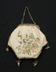 1800 - 1825 Reticule English Cream silk satin reticule with handpainted flowers in naturalistic colours and a silver linked chain handle. It is trimmed with silver lace with 4 tassels in the shape of pine cones of silver and green foil attached with loops of silver thread. It has a spring catch.  CollectionSnowshill Wade Costume Collection, Gloucestershire