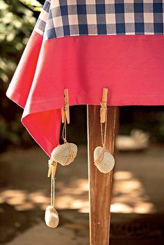 O objetivo principal é de ordem prática: evitar que a toalha alce voo num encontro ao ar livre. Mas estes pesos feitos com seixos também vêm como bônus de dar mais bossa à mesa. Amarre as pedras comum barbante de ráfia e prenda o fio em um pregador de roupas. Não se preocupe em fazer uma amarração toda certinha: o efeito emaranhado é bem-vindo