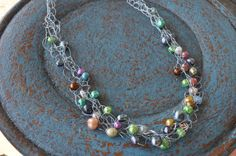 $42.00 22 inch wire crocheted necklace with 45 multi-colored freshwater pearls. Metal is silver colored wire which will not tarnish. Toggle clasp is base metal. Dress it up or wear it with denim - looks great either way!