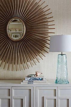 Sunburst Mirror. Dining room sunburst mirror. Against a Phillip Jeffries wallcovering, a mirror from Pineapples, Palms, Etc. anchors the dining room, while seafoam-hued glass lamps reference the water outside. Underneath the setting is a cabinet from Asian Accents of Palm Beach. #Sunburst #Mirror