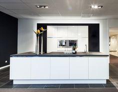 Deze luxe greeploze hoogglanzende Motivo eilandkeuken is uitgevoerd in de kleur wit met een 4 cm dik Simacore werkblad met een zwart matte uitstraling. De keuken is voorzien van het Bora afzuigsysteem, waarbij de afzuiging is verwerkt in de kookplaat.