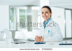Female doctor working at office desk and smiling at camera, office interior on background