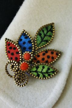 "Felt ""leaf"" brooch enveloped with pieces of brass zipper.The leaves have been embellished with hand embroidery using a shade of green, orange and turquoise sweater felt.The approx dimensions of the brooch are 2"" x  3"".There are two orange felt beads wrapped in brass zipper at the base of the brooch.The leaf brooch is light weight and quite firm."