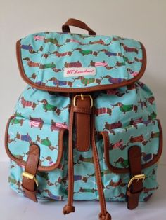 A turquoise blue backpack rucksack patterned with cute Dachshund dogs wearing glittery jumpers premium quality thick canvas fabric with faux leather