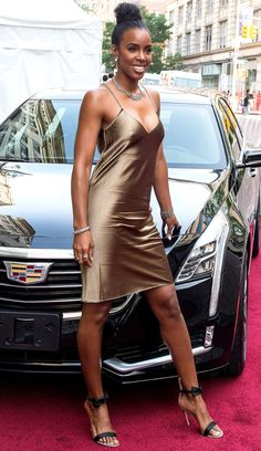 KELLY ROWLAND in a bronze satin slip dress and black ankle-strap heels