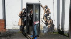 Banksy is believed to be behind a piece of street art depicting three shadowy figures eavesdropping - three miles from the Government listening post GCHQ.
