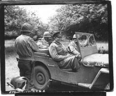 Einsenhower and Bradley while as they say good bye to Maj. Gen. Ira Wyche, back to camera, commanding general 79th div., after a visit to general Wyche's headquarters in France. 4/7/44. Haunville, France