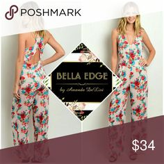 Blush bold floral jumpsuit 100% RAYON. This beautiful jumpsuit features bold and bright red, blue and cream floral print over blush which compliments any skintone. V-neckline, open low back, and criss-cross back straps. Sizes small to large.  Ships Thursday 7/8 Bella Edge Boutique  Pants Jumpsuits & Rompers