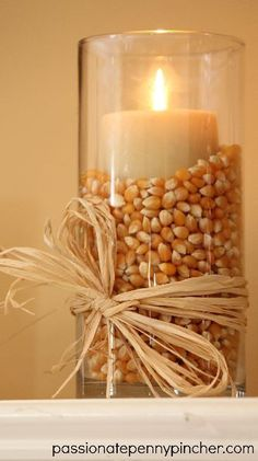 I love popcorn....I could do this with those candle sticks that have a liner between the candle & the outside...or use that round centerpiece bowl....upside down with the inner circle filled with acorns etc.