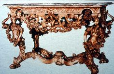 The easiest way to show your wealth is to show your possesion of gold and silver. This is a French gilt table. The shape is also exaggerated with emphasis on weight. The table legs are women with almost broken backs to carry the weight of the marble slab