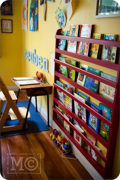 I've seen libraries with shelving like this, but it hadn't crossed my mind that it would work at home. (From an article about kids' writing centres.)