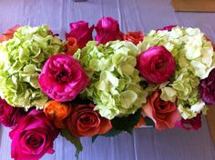 Spring Centerpiece that I made with bright pink & orange roses, green hydrangeas, orange ranunculus and white fresia.