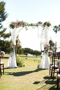 traditional floral wedding arch with curtains and pink roses