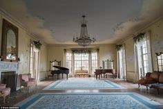 Traces of the mansion's opulent past remain: Two grand pianos, a chandelier and even the  carpets suggest how the room once looked