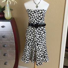"""David Meister BRAND NEW floral dress David Meister BRAND NEW black and white dress in a beautiful floral pattern.  Includes black patent belt.  Strapless design and fully lined. Never worn but had dress dry cleaned to press out wrinkles. Tags still attached   Great condition there is a little fabric pull next to the zipper as pointed out in picture and dry cleaners cut off interior strings that hang on hanger. Measures 34"""" long 16.5"""" across bust 15"""" across waist David Meister Dresses…"""