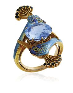 AN ART NOUVEAU SAPPHIRE AND ENAMEL RING, BY RENÉ LALIQUE. Centering an oval-cut sapphire between two peacock heads applied with blue and black enamel, circa 1900, ring size 5 ½, with French assay mark for gold. Signed Lalique. SSEF / the origin of the sapphire is Ceylon (Sri Lanka), with no indications of heating. #RenéLalique #ArtNouveau #Jewelry #Jewellery #BijouxArtNouveau