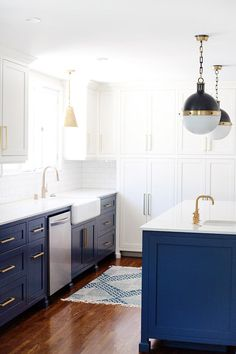 Stunning modern kitchen with royal blue cabinents, gold hardware and large pendant lights