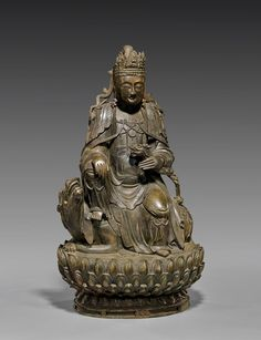 """Large and heavy, Chinese Ming-style bronze figure: of a Bodhisattva, wearing an ornate crown with a miniature Buddha, holding a dragon armrest, and seated in the position of """"Royal Ease"""", on the back of a qilin, upon a tiered lotus form base; H: 17 1/2"""""""