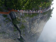 TZHANGJIAJIE, CHINA - AUGUST 01: Aerial view of tourists walking on the 100-meter-long and 1.6-meter-wide glass skywalk clung the cliff of Tianmen Mountain (or Tianmenshan Mountain) in Zhangjiajie National Forest Park on August 1, 2016 in Zhangjiajie, Hunan Province of China. The Coiling Dragon Cliff skywalk, featuring a total of 99 road turns, layers after another, is the third glass skywalk on the Tianmen Mountain (or Tianmenshan Mountain). (Photo by VCG/VCG via Getty Images) via…