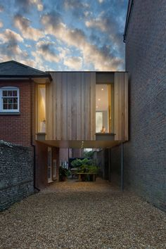 """""""British architect Adam Knibb has extended a house in a converted school in Winchester, England, by building a timber box above a seldom-used driveway. Architecture Design, Amazing Architecture, Wooden Cladding, Architects Journal, Building A Porch, Brick Facade, London House, Timber House, House With Porch"""