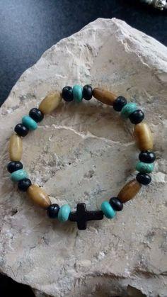 Armband gemaakt met turquoise kralen, zwarte houten kralen, kralen gemaakt van bot en een zwart kruisje.