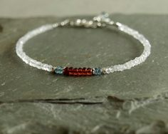 This natural gemstone bracelet has smooth red garnet at its center, surrounded by rare ice blue kyanite, small white moonstone, and sterling silver beads. The bracelet closes with a sterling silver lobster clasp, with a kyanite stone and very small heart charm hanging from the closure chain. Great for stacking or on its own, the small gemstones in this bracelet have a touch of unusual mystery -- from the tiny sparkle and flash of the small roughly faceted moonstone to the translucence in the…