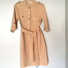 Cute Shirt Dress This is a really cute button-down shirt dress with 3/4 length sleeves. The color is a combination of peach/tan/khaki. Button detailing on the sleeves, pockets, and the shoulders. Comes with matching belt and has belt loops on the sides. // Cato brand // Sz 12 // non-smoking home Cato Dresses Midi