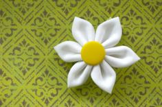 How to make a fabric daisy flower {tutorial}.  These would be adorable on a little girl's dress or on a headband or hair bow.