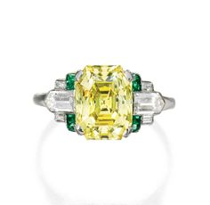 PLATINUM, FANCY VIVID YELLOW DIAMOND, DIAMOND AND EMERALD RING.  The rectangular step-cut Fancy Vivid Yellow diamond weighing 3.30 carats, flanked by six baguette and bullet-shaped diamonds weighing approximately .55 carat, further accented by eight calibré-cut emeralds, size 6½, circa 1920.