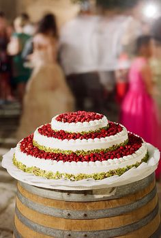 Round, three-tiered wedding cake with fresh wild strawberries and tiers encrusted with pistachios. (Photo: Kate Headley). Rustic wedding