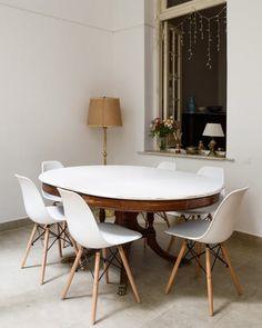 Mesa antigua reciclada y sillas eames blancas.